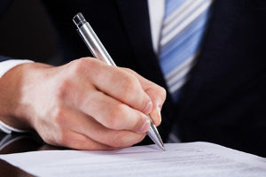 businessman signing proof of employee-employee relationship for H-1B visa