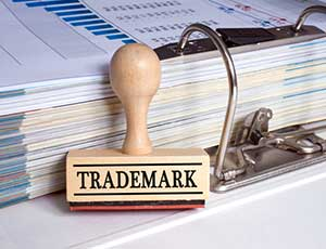 Trademark stamp next to papers needed to file a trademark infringement lawsuit