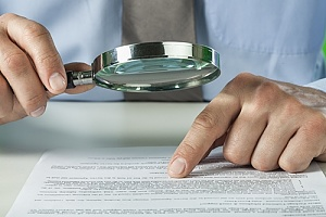 Person carefully reading document with magnifying glass